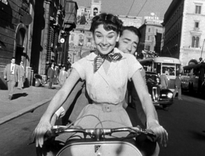 https://upload.wikimedia.org/wikipedia/commons/6/65/Audrey_Hepburn_and_Gregory_Peck_on_Vespa_in_Roman_Holiday_trailer.jpg